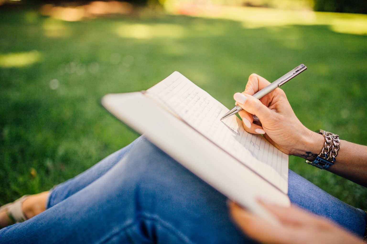 Writing - Woman's hand writing with a pen in a paper journal