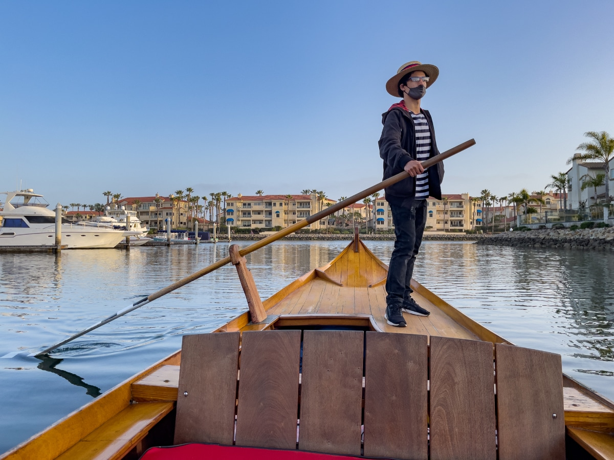 Beautiful Oxnard gondolier at the helm of gondola in Channel Islands Harbor